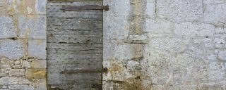 Small sturdy wooden door in a castle wall
