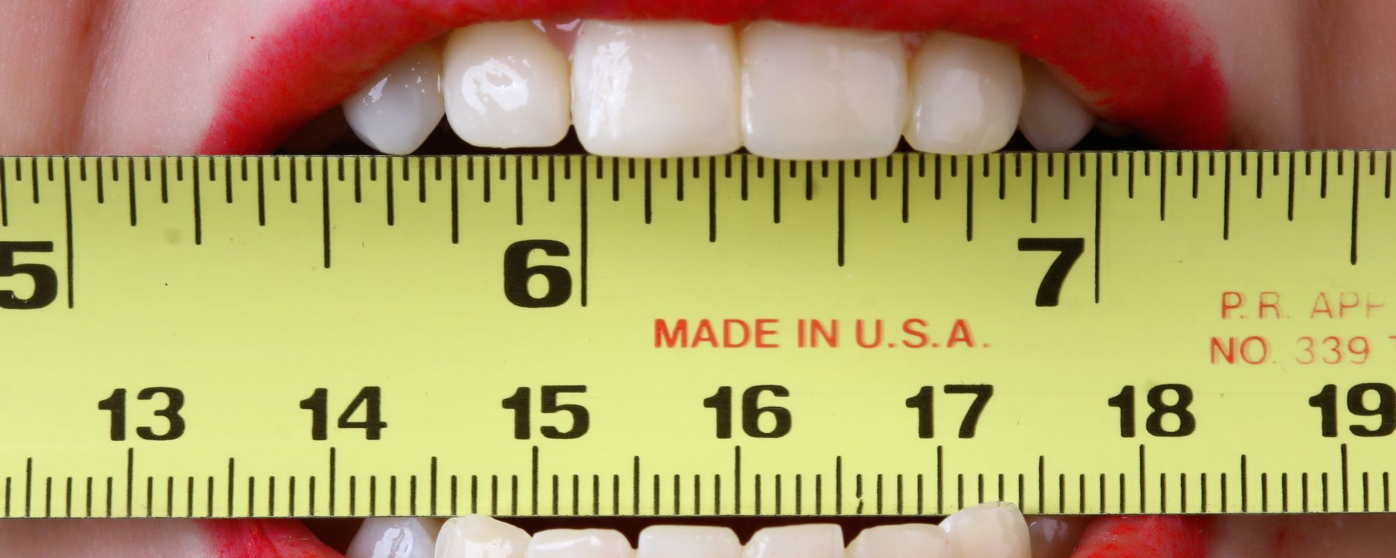 Close up on a woman's teeth biting a measuring tape