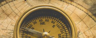 Detail of an antique compass placed on a map