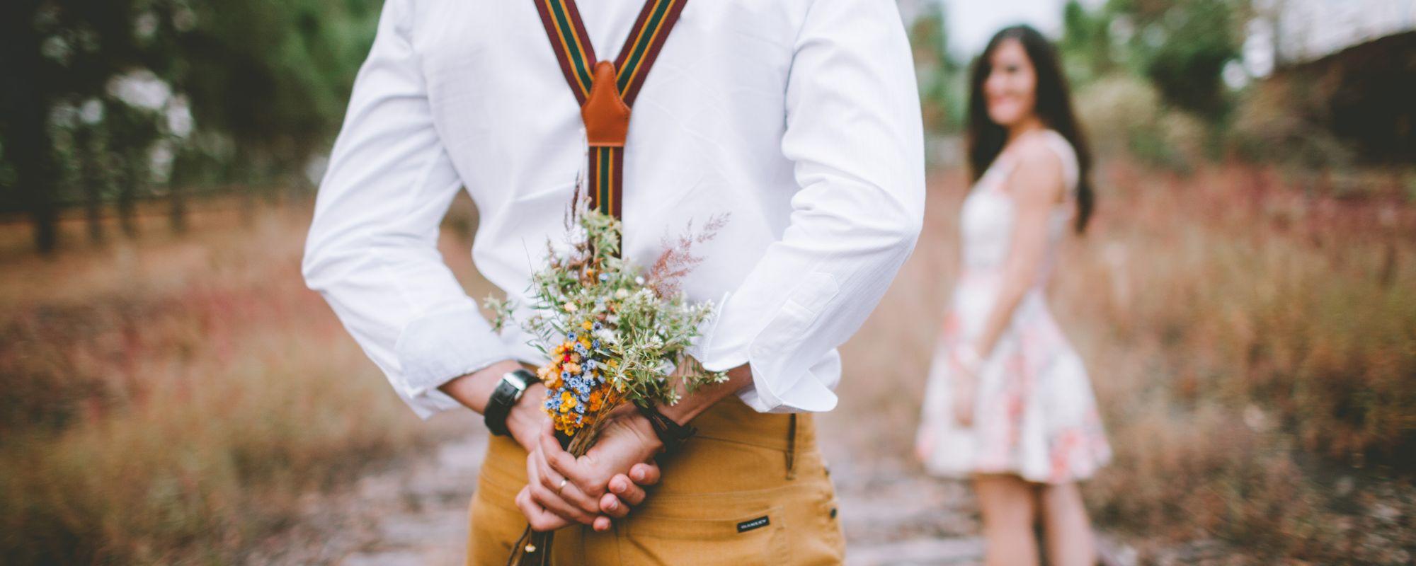 Barbat care ascunde florile de prietena.