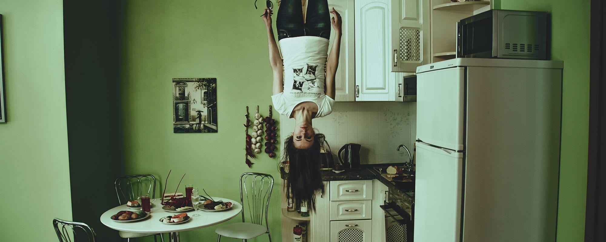 Femeie cu capul in jos in bucatarie